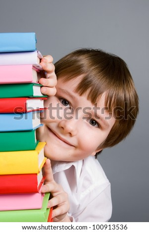 Boy looks out from a stack of books on a gray background - stock photo