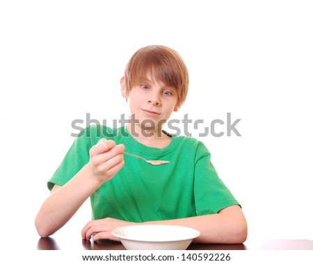 Boy Looks Skeptically at the Food He's Been Given (green shirt for easy color replacement) - stock photo