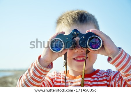boy looks through binoculars and sees sea - stock photo