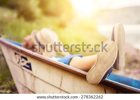 Boy lying in old boat in the lake coast close up image - stock photo