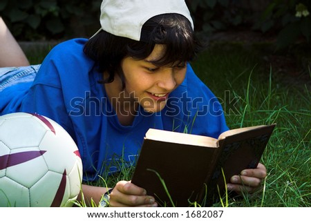Boy lying next to his football, reading with a smile - stock photo