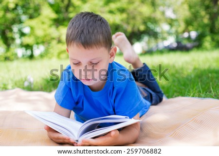 Boy lying on beach mat and reading book seriously. Selective focus - stock photo