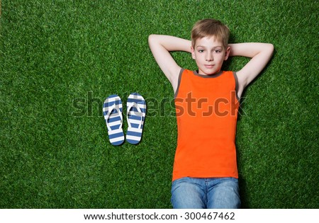 Boy lying on green grass with slippers - stock photo