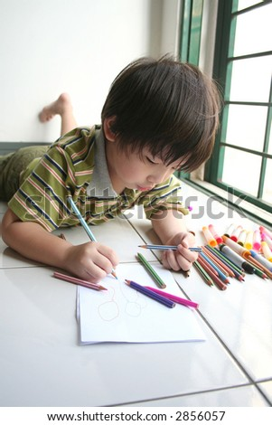 Boy lying on the floor and drawing on the art paper - stock photo