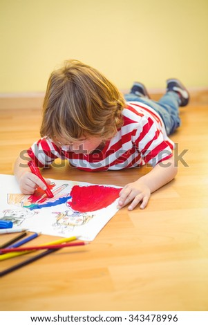 Boy lying on the ground colouring his picture - stock photo