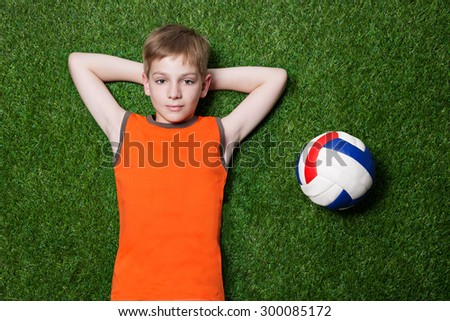 Boy lying with ball on green grass close up