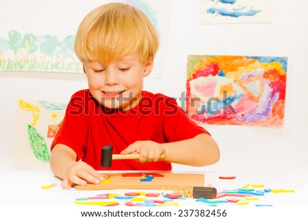 Boy make picture with hammer nails and blocks - stock photo