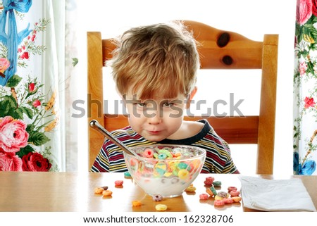 Boy making a face while eating breakfast cereal - stock photo