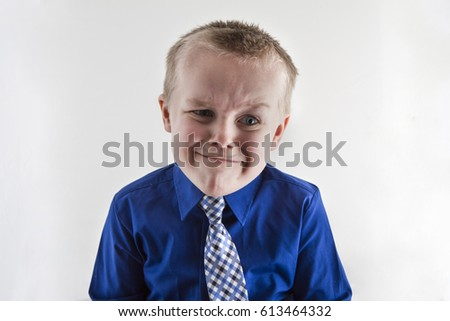 Boy making a funny expression on his face while dressed up in a suit and tie