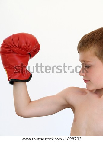 boy making a muscle with a red boxing glove on - stock photo