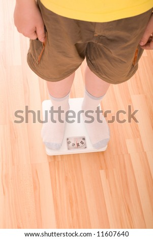 Boy measures weight on floor scales. Legs in shorts and socks standing at floor scales on hardwood floor in living room. View from above. - stock photo