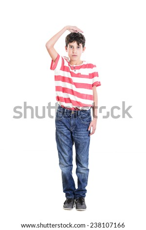 Boy measuring his growth in height - stock photo