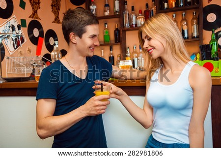 boy meets a girl and treat her cocktail in the bar. horizontal photo - stock photo