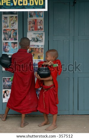 boy monks in burma looking at movie posters and eating ice cream after taking a break from seeking alms