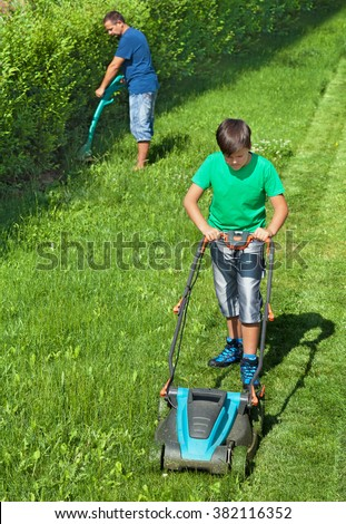 Boy mowing the lawn and man trimming the edges - summer activities - stock photo