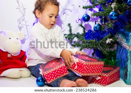 Boy near a Christmas tree with gifts. - stock photo