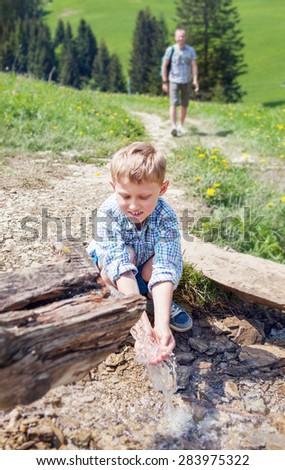 Boy near mountain stream - stock photo