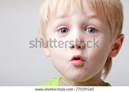 Boy of five years is strongly surprised, close up, background light