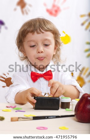 Boy of four years old dressed in a white shirt with red bow is dealing with letters Closeup
