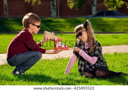 Boy offer girl shoes on the green grass in the park