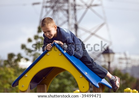 Boy on a playground in city park - stock photo
