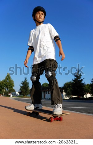 Boy on a skateboard against blue sky looking in the sun - stock photo