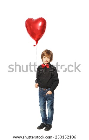 Boy on a white background in a black shirt with a bow tie holding a balloon in the shape of heart - stock photo