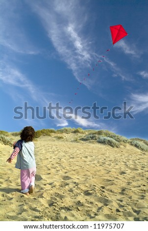 boy on beach playing with a red kite - stock photo