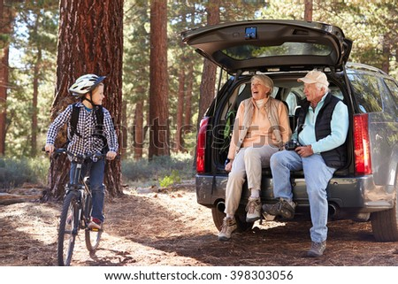 Boy on bike and senior couple in car preparing for a hike - stock photo