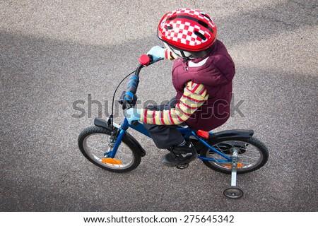 Boy on bike at asphalt road in spring - stock photo