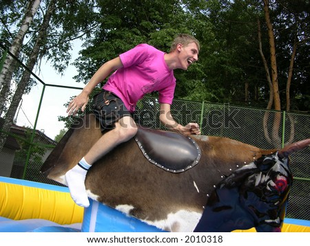 boy on bull simulator - stock photo