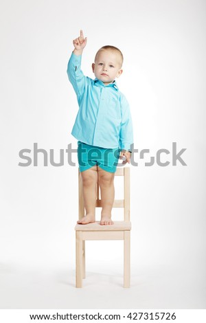 boy on chair and pointing his finger up - stock photo
