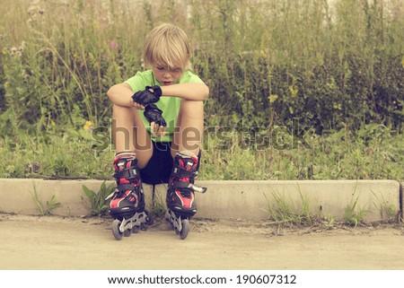 Boy on roller skates sitting on the roadside. - stock photo