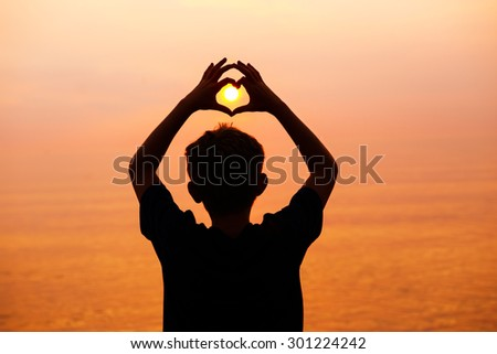 Boy on the beach making a heart shape with his hands at sunset. Main focus on head. - stock photo