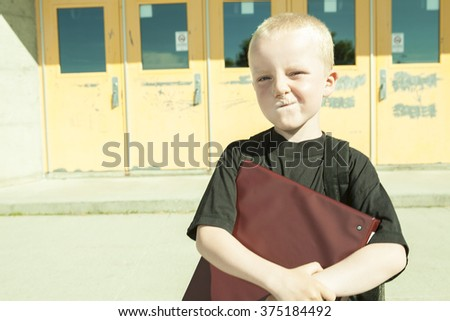 boy on the playground of his school with a backpak - stock photo