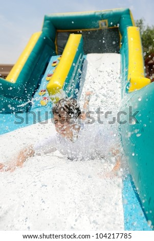 Boy on Water Slide. Boy making a splash as he slides down a water slide.