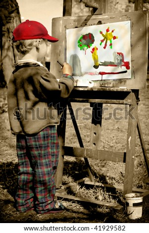 Boy painting his colorful world, outdoors. - stock photo