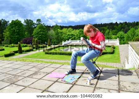Boy painting in a beautiful park with looming storm clouds