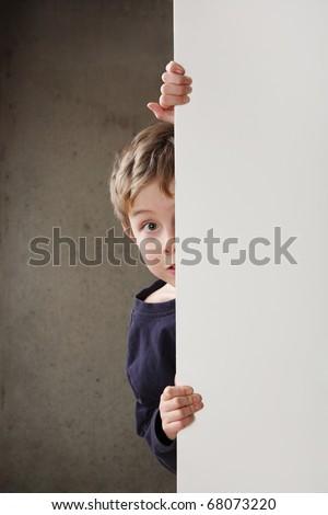 Boy Peeking around a wall - stock photo