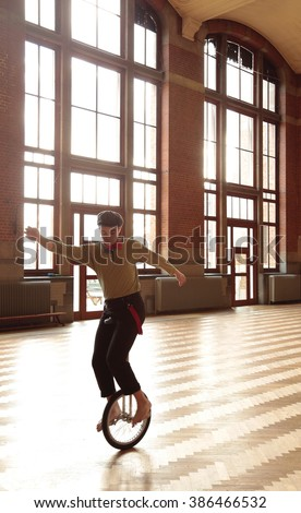 Boy performing with unicycle - stock photo