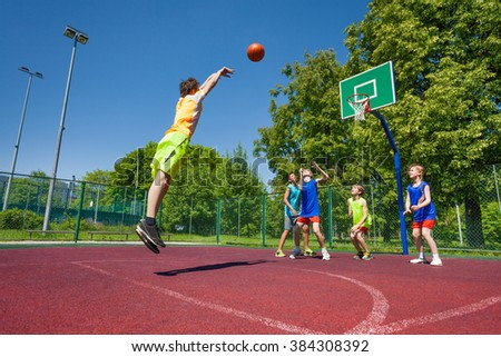 Boy performs foul shot at basketball game on the playground during sunny summer day - stock photo
