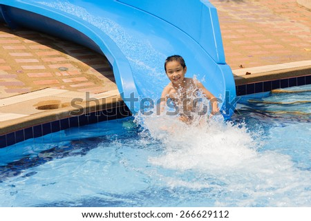Boy play blue slider into the pool - stock photo