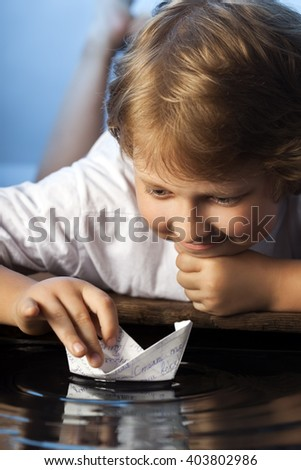 boy play in paper ship in water puddle
