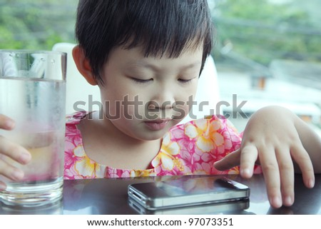 Boy play mobile phone during waiting food. - stock photo