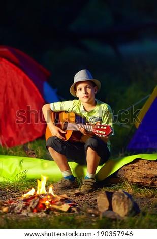 boy playing a guitar near bonfire, summer camp - stock photo