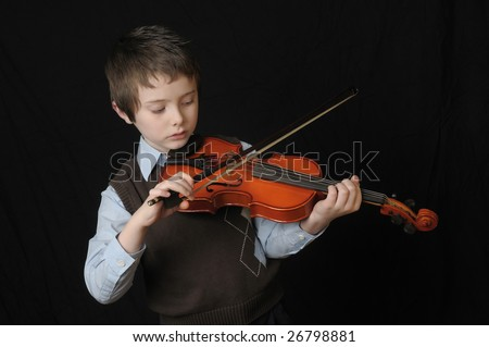 boy playing a Violin isolated over a black background - stock photo