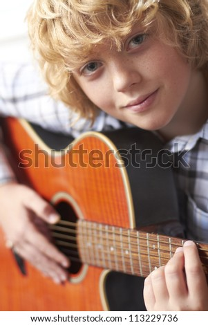 Boy Playing Acoustic Guitar - stock photo