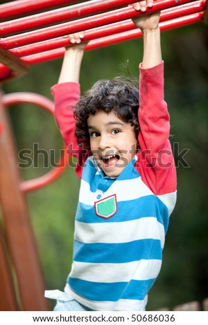Boy playing at the park on the monkey bars and smiling - stock photo