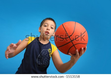 Boy playing basketball isolated. Blue background. From my sport series. - stock photo