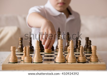 Boy playing chess in the room. Little clever boy concentrated and thinking while playing chess at home. - stock photo